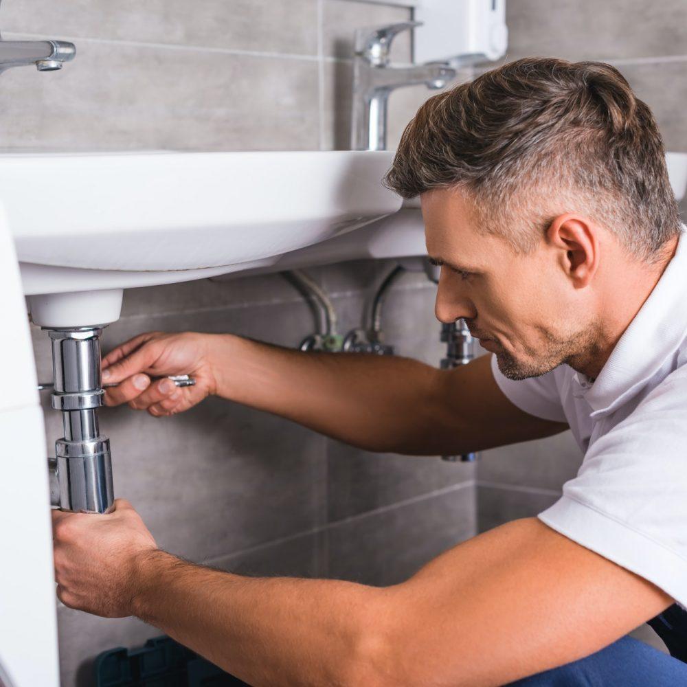 adult-plumber-fixing-sink-at-bathroom.jpg