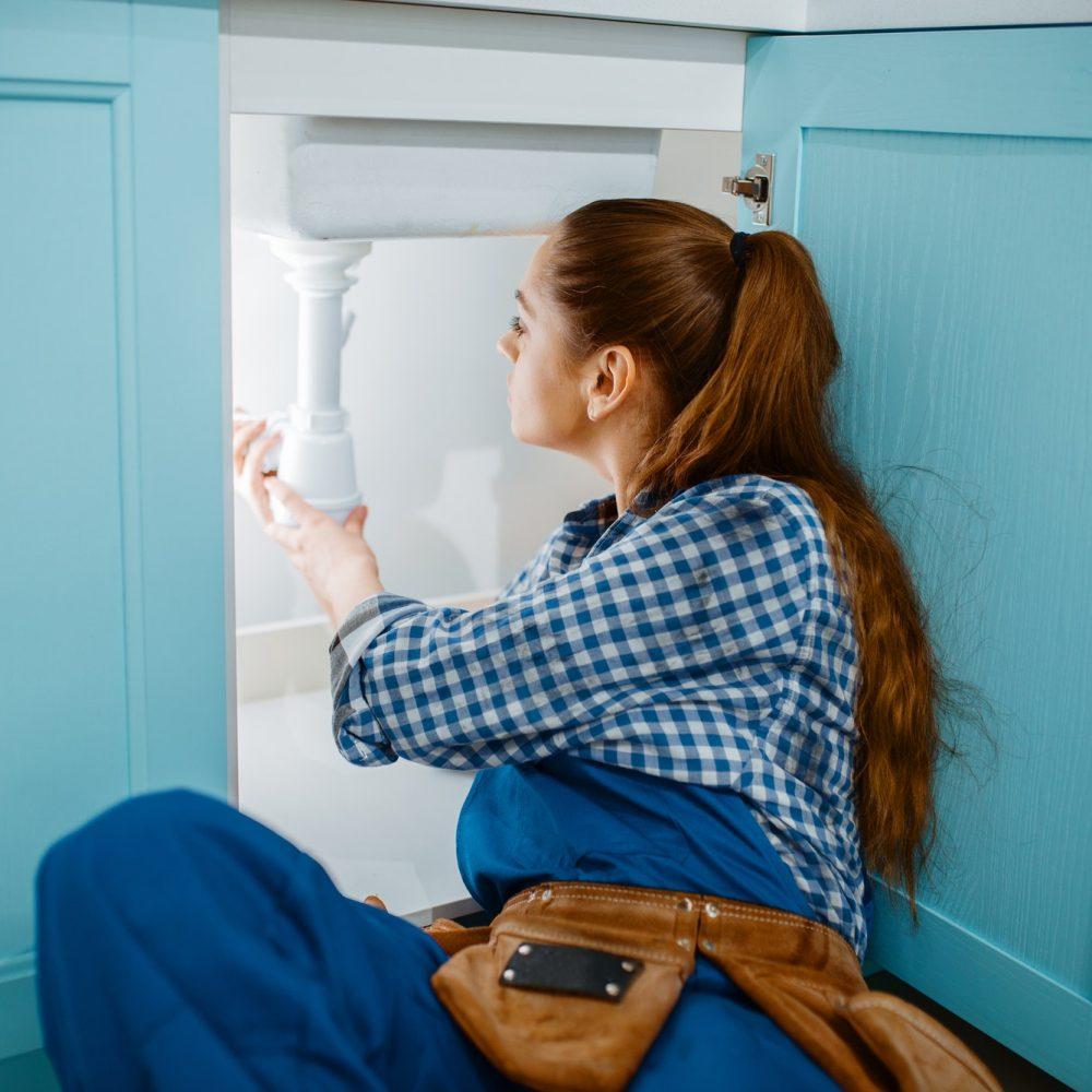 female-plumber-in-uniform-installing-drain-pipe.jpg