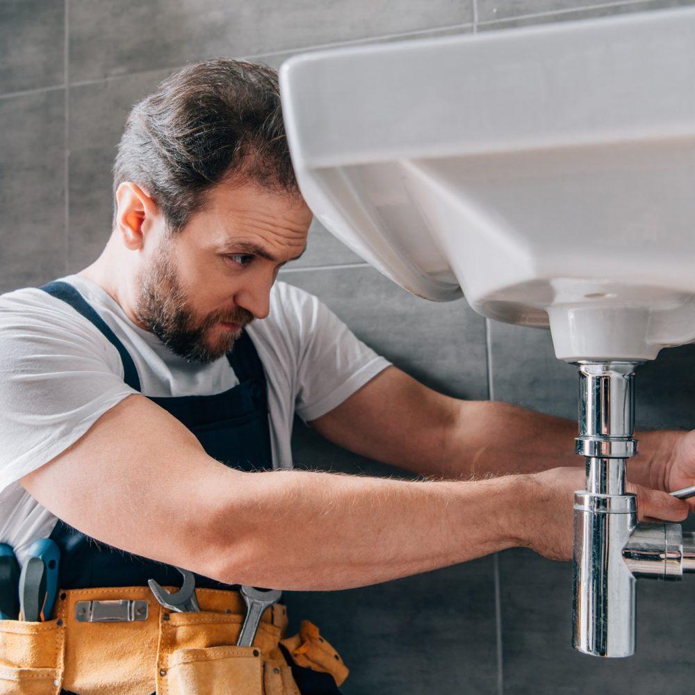 focused-male-plumber-in-working-overall-fixing-sink-in-bathroom.jpg