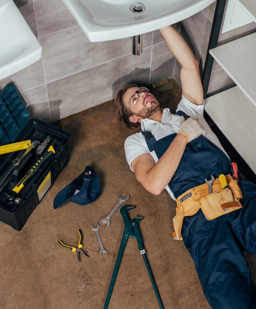 high-angle-view-of-young-male-plumber-fixing-sink-in-bathroom.jpg