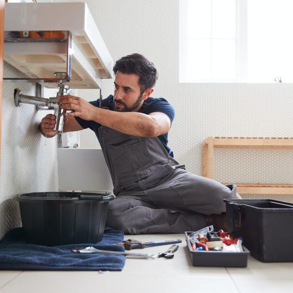 male-plumber-working-to-fix-leaking-sink-in-home-bathroom.jpg