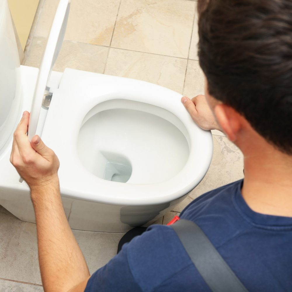the-plumber-in-overalls-fixes-the-toilet.jpg